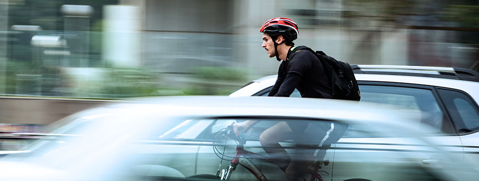 Man riding bicycle through busy traffic