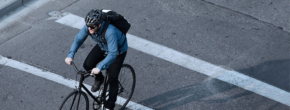 Man riding bicycle to work wearing helmet